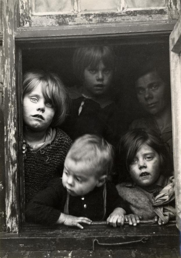 Poor children looking through a window